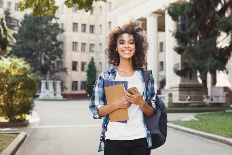 Studentenmädchen mit Rucksack und Mobile am Hochschulgebäudehintergrund stockfotografie