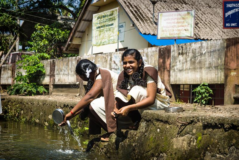 Studentenmädchen waschen ihre Schüsseln entlang des Flusses Kerala im Unterwasserkanal Alleppey - Alappuzha, Indien lizenzfreies stockfoto