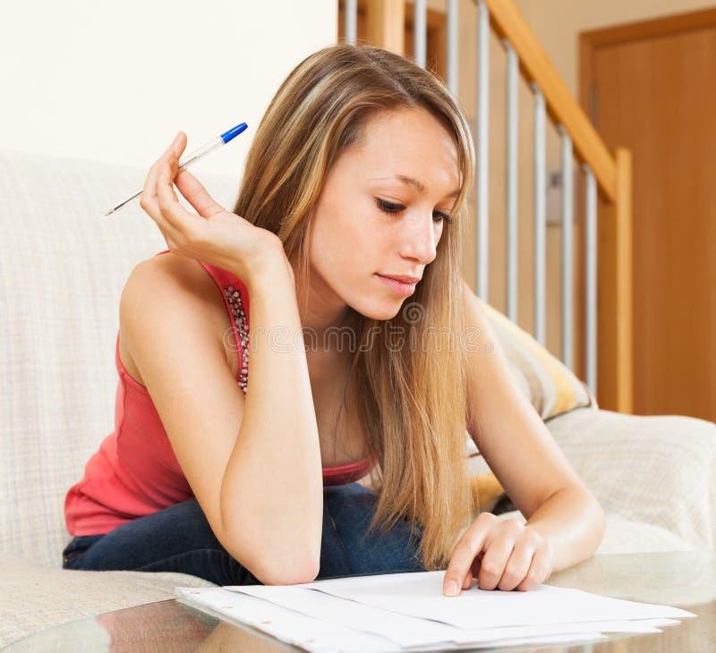 Studentenmädchen, welches sorgfältig die Anmerkungen studiert stockfotos