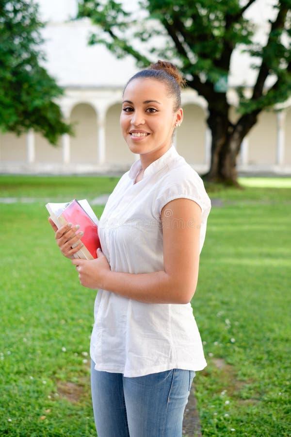 Studentenmädchenporträt, das Bücher inhands hält stockfotografie