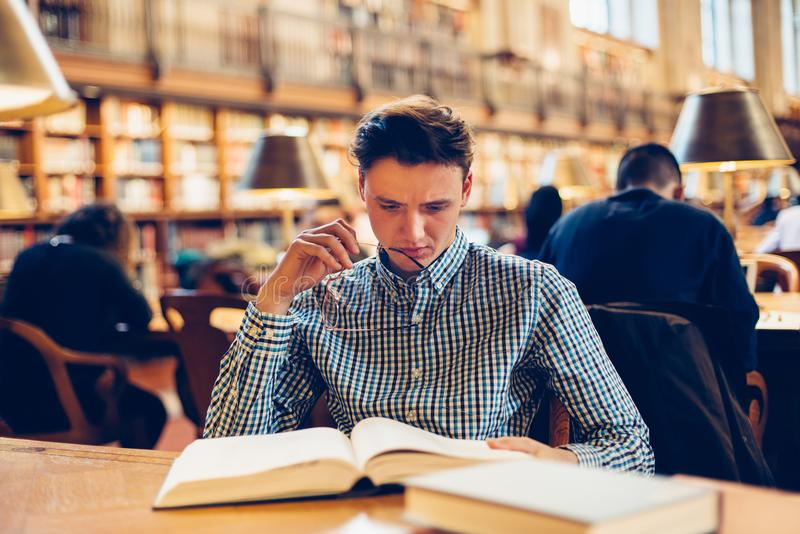 Studentenmann, der auf dem Schreibtisch im Bibliothekslesesaal sitzt und Forschungslesebücher tut stockbild