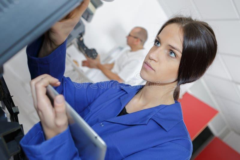 Studentenmechaniker, der Tabletten-PC verwendet stockfotos