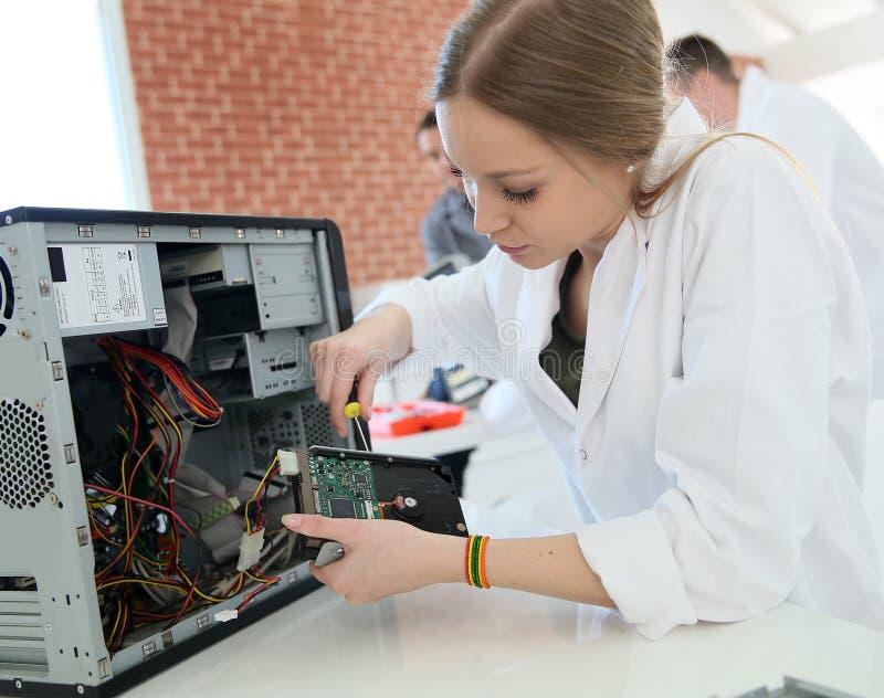 Studentenmeisje in de gegevensverwerking van klasse die harde schijf bevestigen stock afbeeldingen