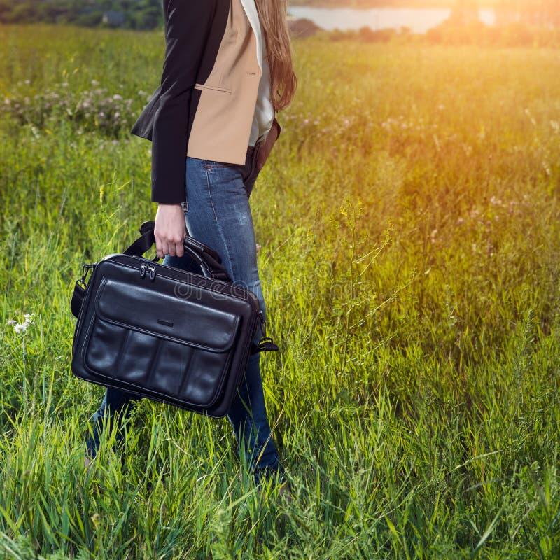 Studentenmeisje die en zwarte leerlaptop gevalzak in openlucht op zonnige groene grasweide lopen dragen stock foto