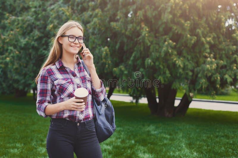 Studentenmeisje die op mobiel met koffiekop spreken royalty-vrije stock afbeelding