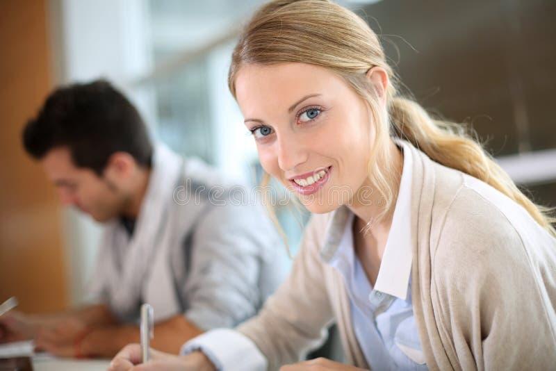 Studentenmeisje in klasse die nota's nemen stock afbeelding