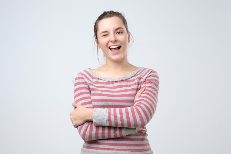 Studentenmeisje knipogen die in camera met het blije gezichtsuitdrukking lachen kijken stock fotografie