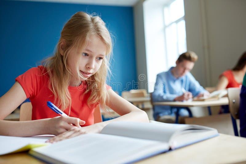 Studentenmeisje met boek het schrijven schooltest stock fotografie