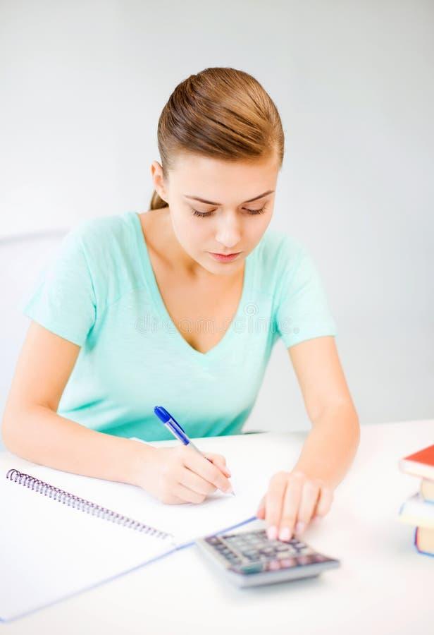 Studentenmeisje met notitieboekje en calculator stock fotografie