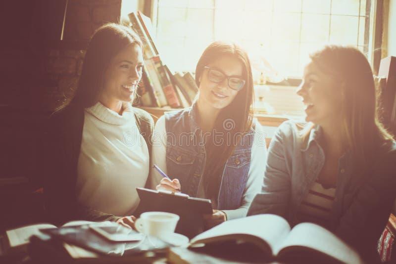 Studentenmeisjes die en in bibliotheekkoffie spreken leren royalty-vrije stock foto
