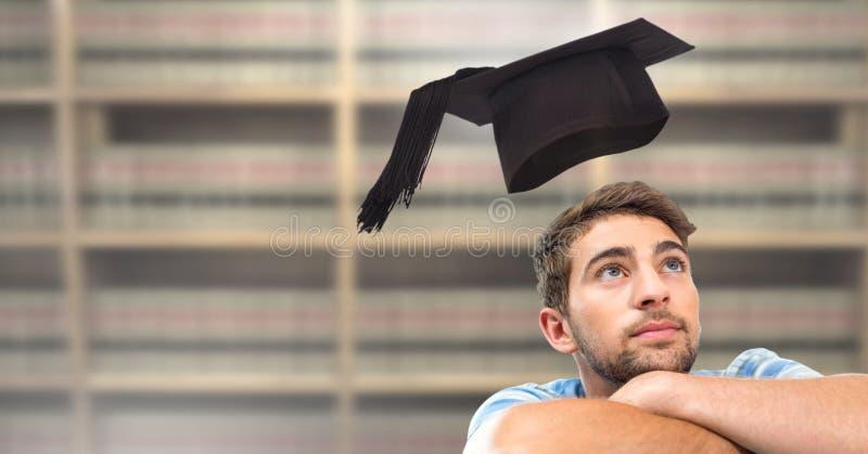 Studentenmens in onderwijsbibliotheek met graduatiehoed stock fotografie