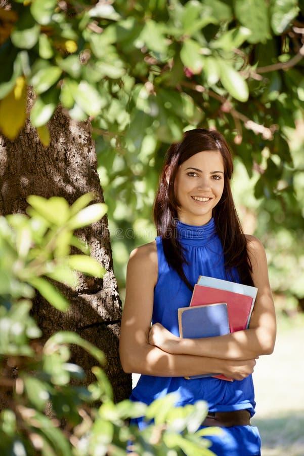 Studentenporträt an der Schule, glückliche junge Frau mit Universität BO stockfotografie