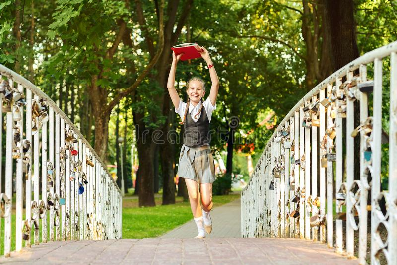 Studentenschoolmeisje gelukkig met vlechten in eenvormig met boeken in handen boven hoofdlooppas over brid stock afbeeldingen