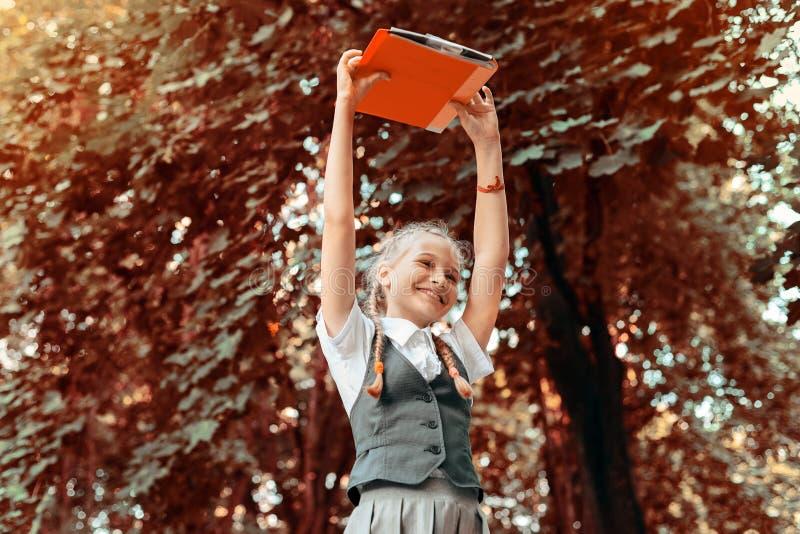 Studentenschoolmeisje gelukkig met vlechten in eenvormige holdingsboeken in handen lucht royalty-vrije stock afbeelding