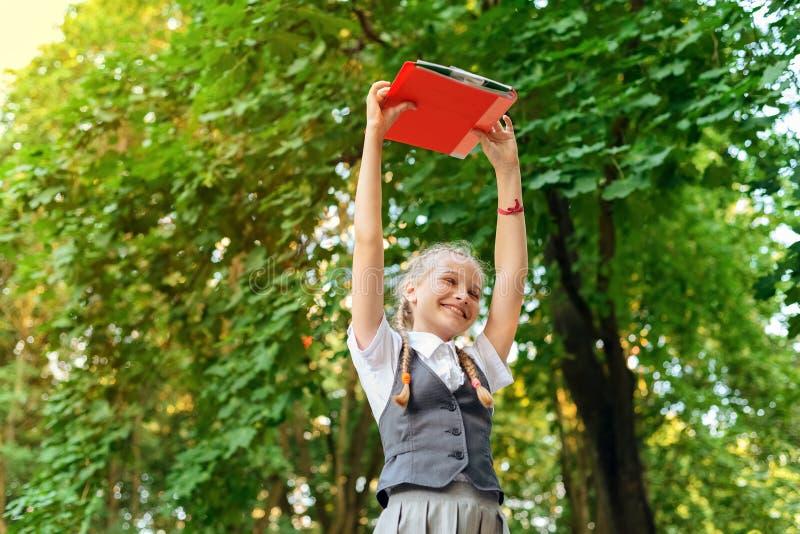 Studentenschoolmeisje gelukkig met vlechten in eenvormige holdingsboeken in handen lucht royalty-vrije stock fotografie