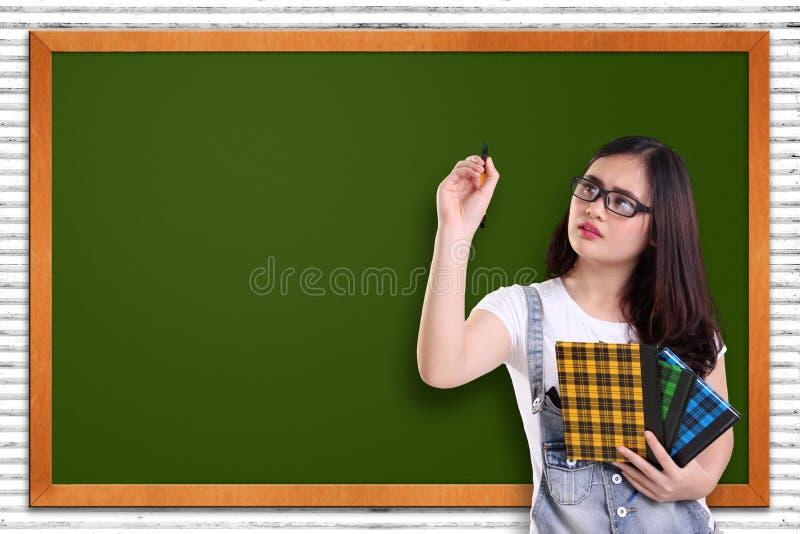 Studentenschreiben auf leerer Tafel lizenzfreie stockbilder