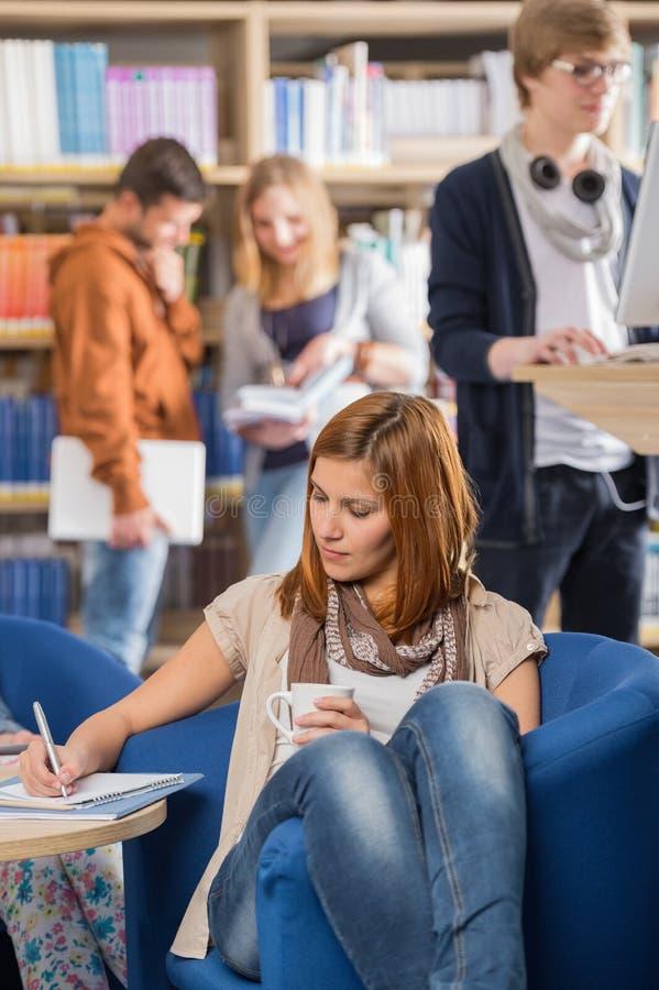Studentenschreibensanmerkungen in der Bibliothek stockfotografie