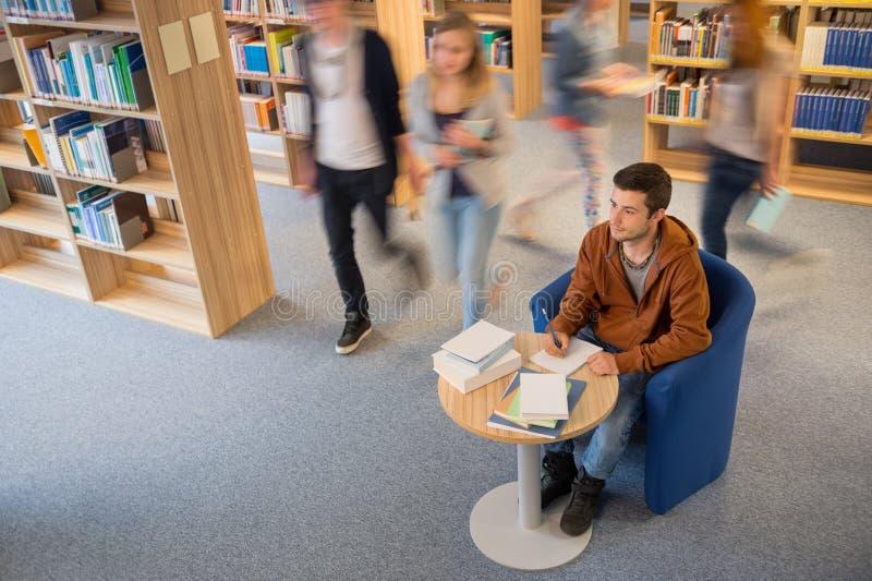 Studentenschreibensanmerkungen in der Bibliotheksunschärfebewegung stockbilder