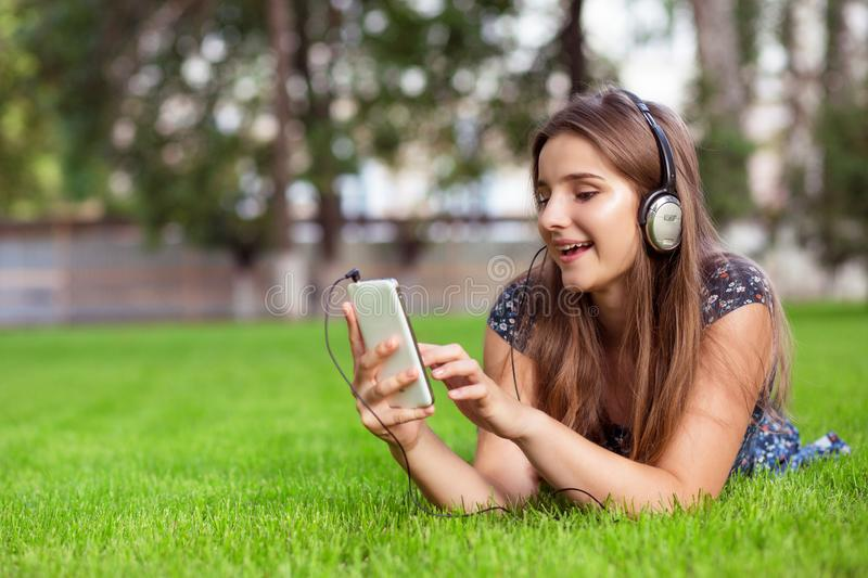 Studentenvrouw die smartphone, hoofdtelefoon op hoofd gebruiken die aan muziek in openlucht luisteren stock foto