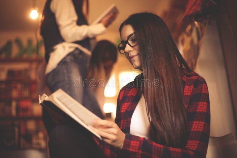 Studentenzitting neer in bibliotheek en lezingsboek royalty-vrije stock afbeelding
