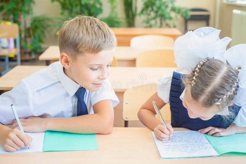 Studenter eller klasskompisar i skolaklassrumet som tillsammans sitter på skrivbordet royaltyfri foto