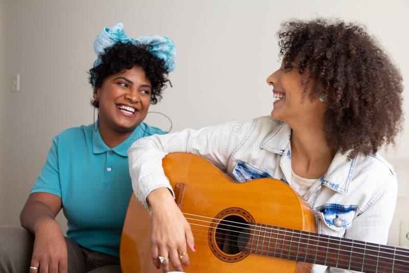 Studenter från högskolan spelar gitarr och sjunger tillsammans i en liten lägenhet i vardagsrummet Fuktiga och lyckliga tider arkivbilder