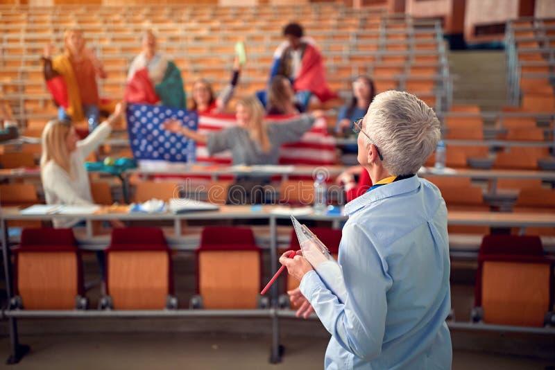 Studenter framlägger landet med flaggan på universitetsområde arkivbild