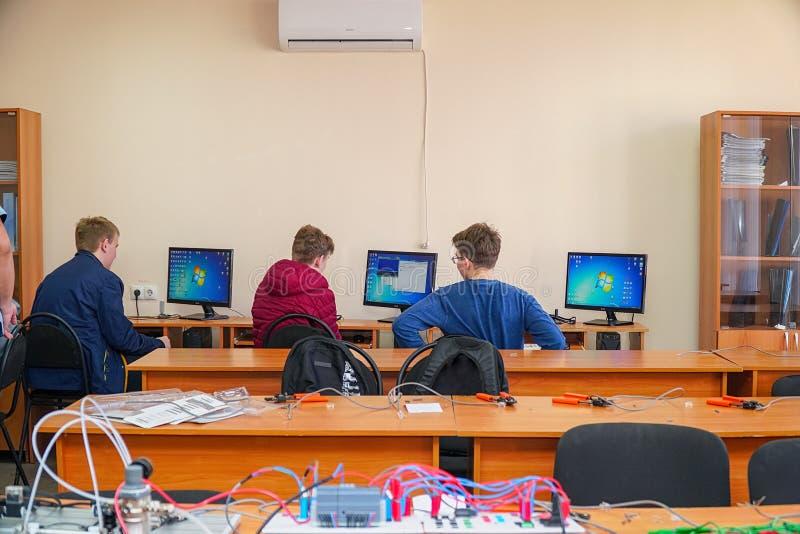 Studenter framme av datorer i en datorgrupp royaltyfri foto