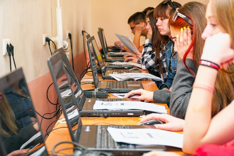 Studenter framme av datorer i en datorgrupp royaltyfria foton