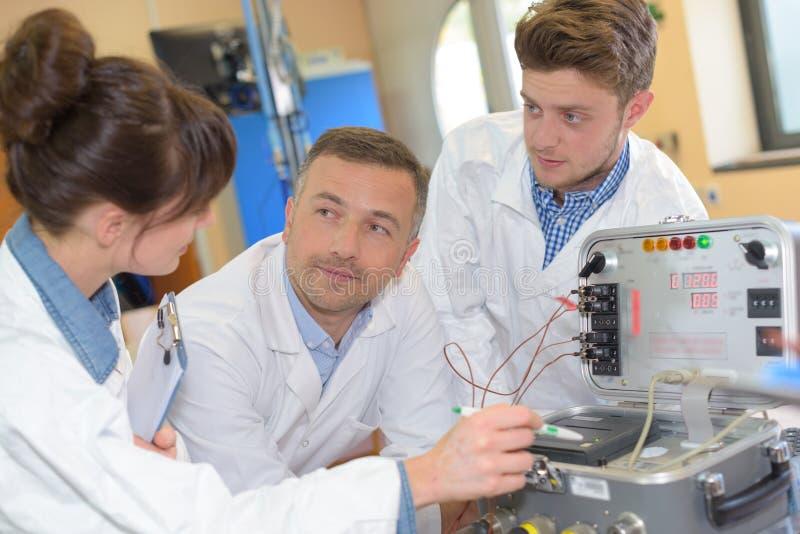 Studenter i elektroteknikkursutbildning med läraren arkivfoto