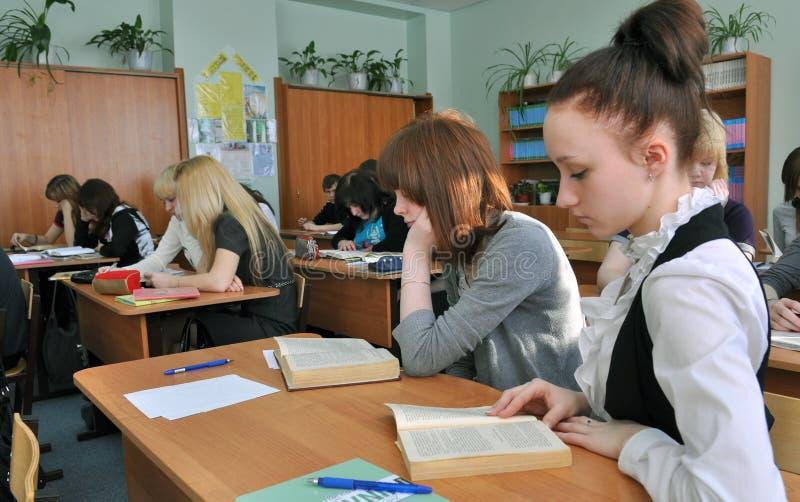 Studenter i gruppen läste försiktigt läroböckerna i klassrumet royaltyfri bild