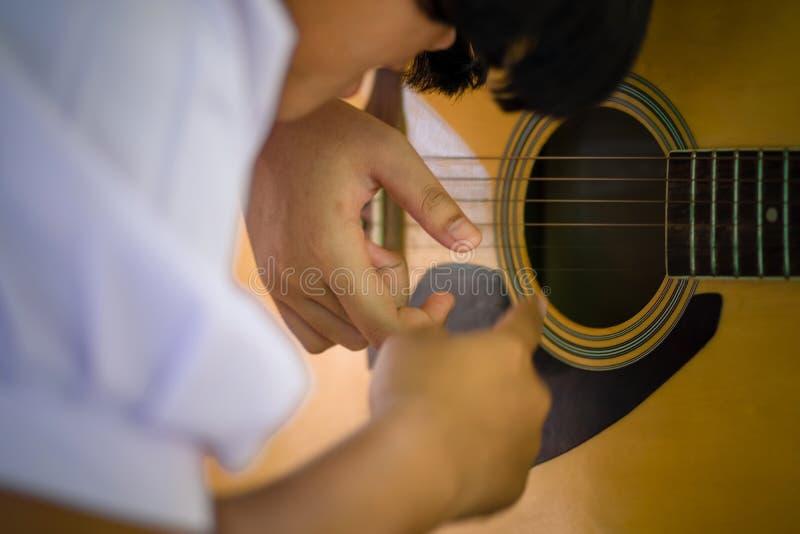 Studenter lär hur man spelar gitarren i skola arkivfoton