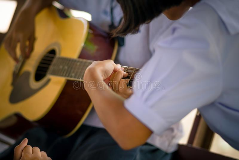 Studenter lär hur man spelar gitarren i skola royaltyfri bild