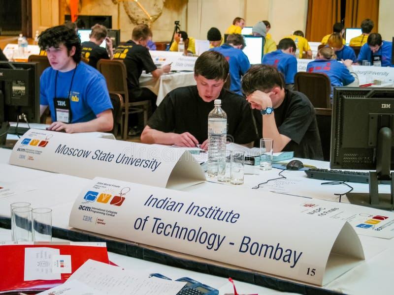 Studenter löser uppgifter på den internationella college- programmera striden arkivbild