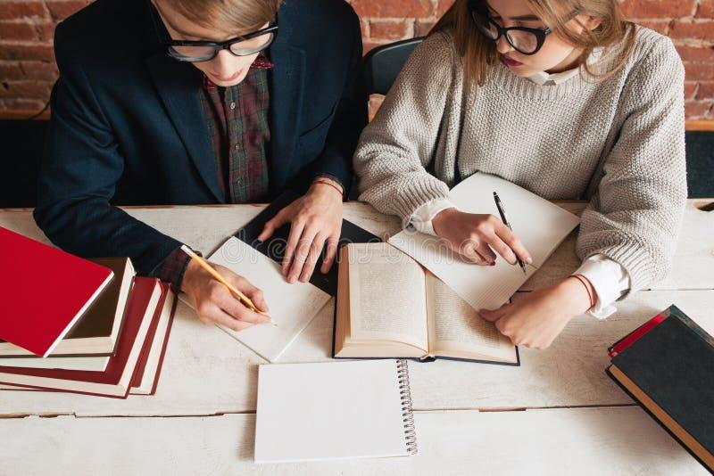 Studenter man, och kvinnan rekapitulerar bästa sikt för text royaltyfri fotografi