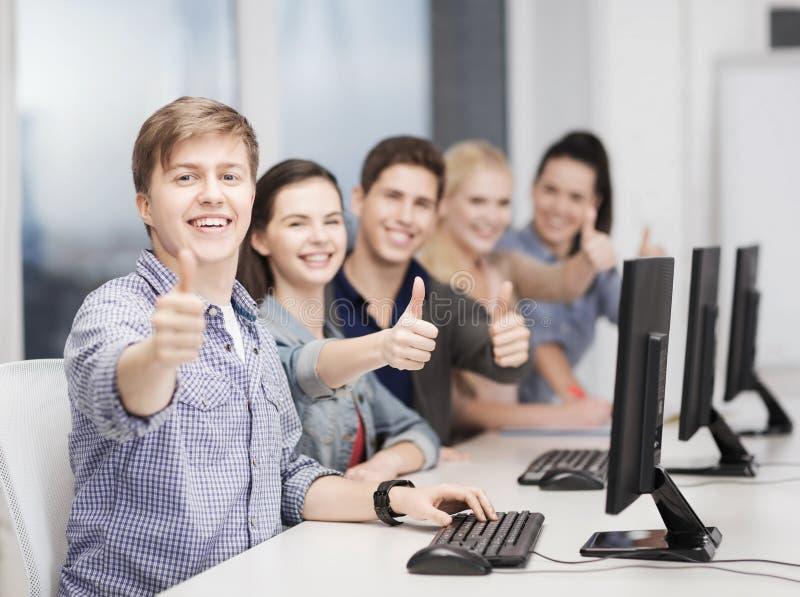 Studenter med datorbildskärmvisning tummar upp royaltyfri bild