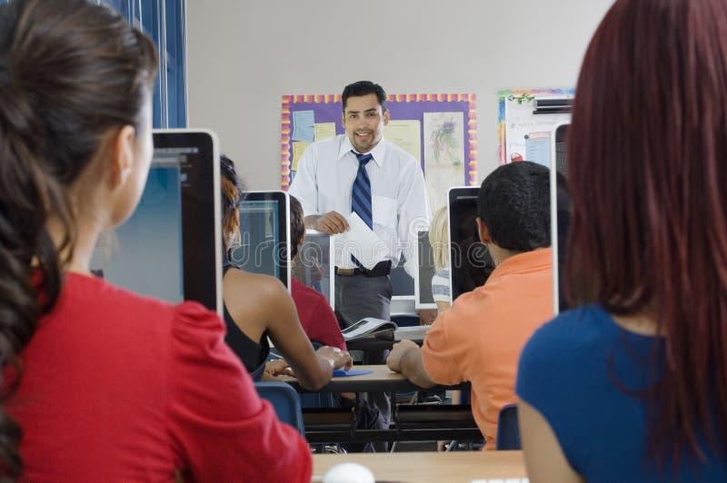 Studenter med professorn In Modern Classroom arkivbilder