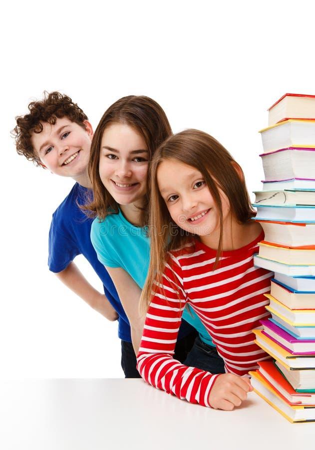 Studenter och hög av böcker arkivfoto