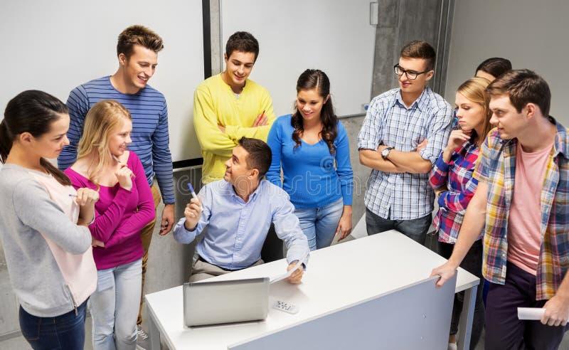 Studenter och lärare med legitimationshandlingar och bärbara datorn arkivbild