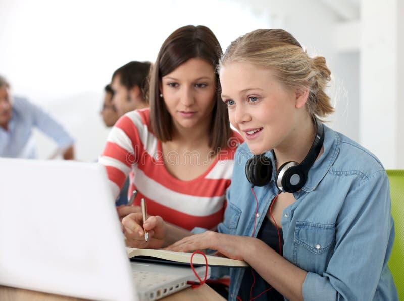Studenter som arbetar i lag i klassrum arkivfoton
