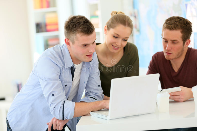 Studenter som arbetar på bärbara datorn arkivfoto