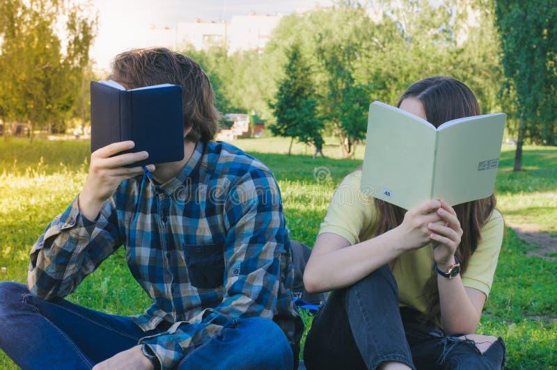 Studenter som döljer framsidor bak böcker Studera för tonåringar arkivbilder