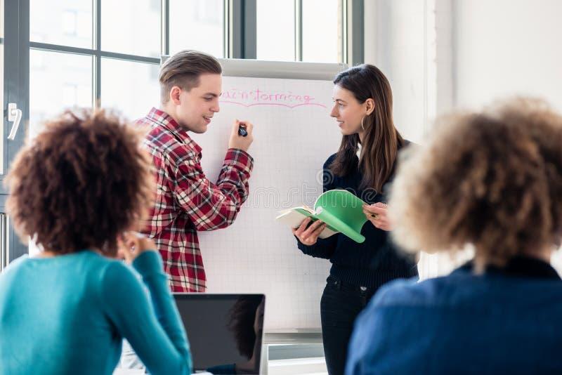 Studenter som delar idéer och åsikter medan idékläckning under a arkivfoto