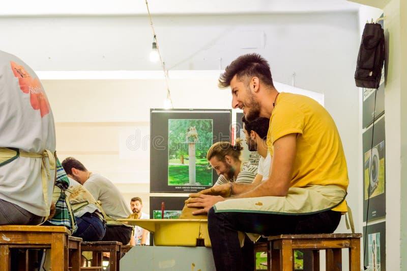 Studenter som deltar i till krukmakerit, bekämpar på symposiet royaltyfri bild