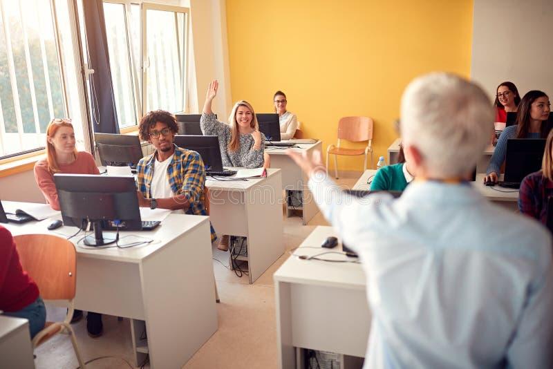 Studenter som frågar fråga, medan delta i föreläsning i universitetsområde royaltyfri fotografi