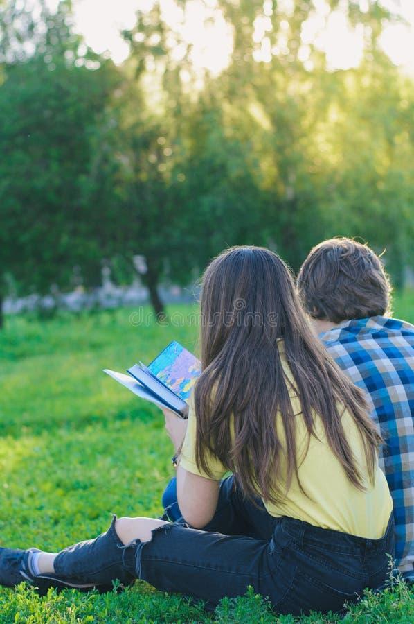 Studenter som håller ögonen på på böcker på den gröna gräsmattan arkivbilder