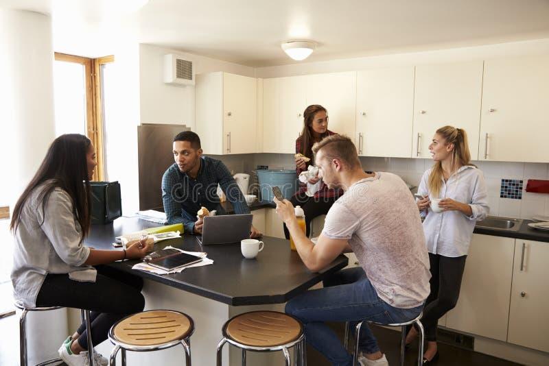 Studenter som kopplar av i kök av delat boende royaltyfri foto