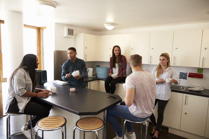 Studenter som kopplar av i kök av delat boende royaltyfri bild