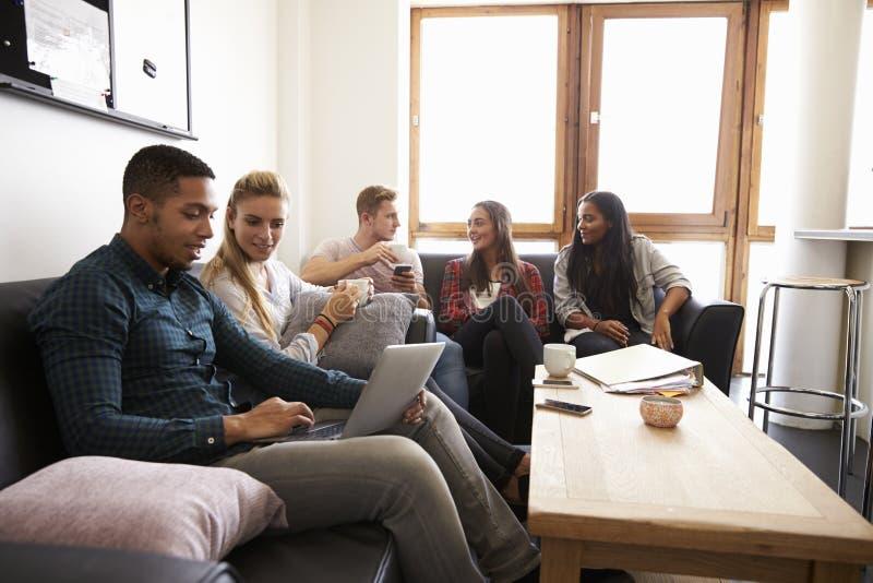 Studenter som kopplar av i vardagsrum av delat boende fotografering för bildbyråer
