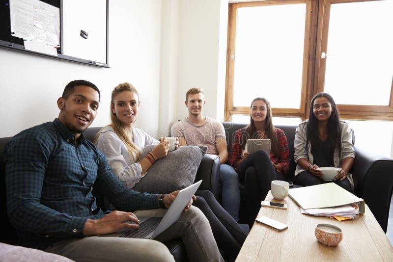Studenter som kopplar av i vardagsrum av delat boende royaltyfria bilder